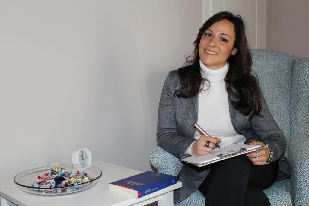 Dottoressa Maria Luongo Psicologo Psicoterapeuta, PhD, CTP seduta in poltrona che scrive