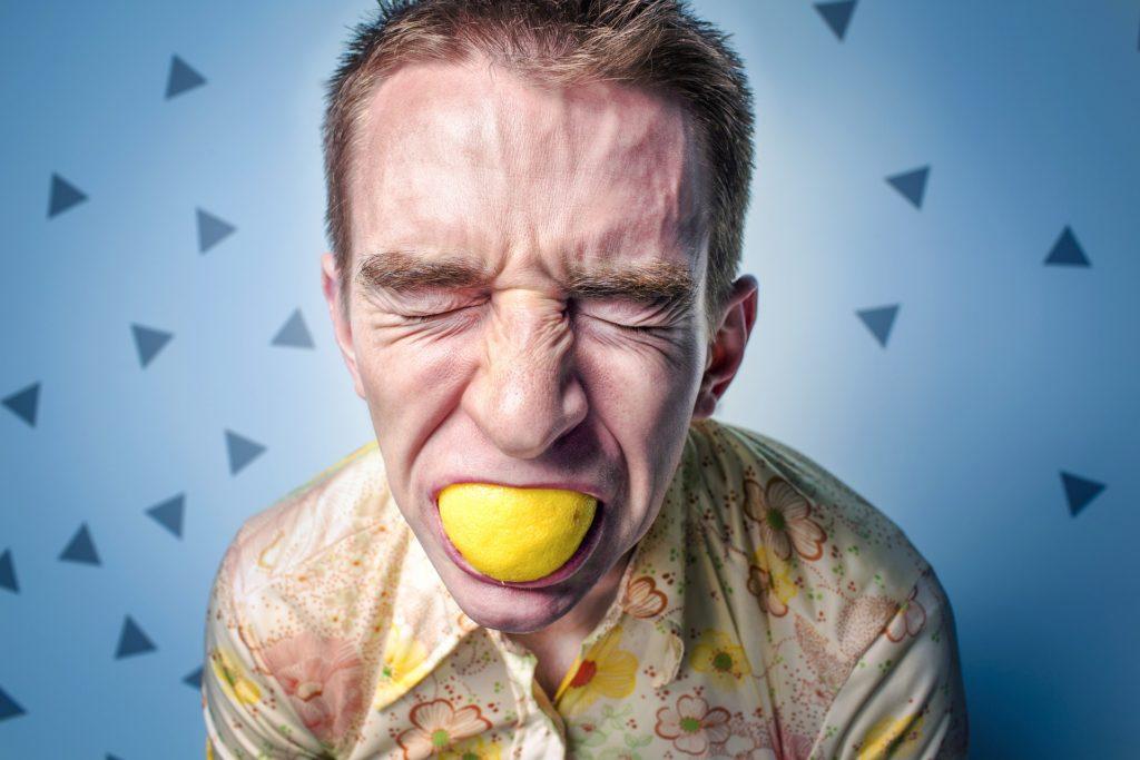 uomo stressato con limone in bocca
